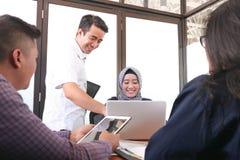 Multiethnische Gruppe glückliche Geschäftsleute, die zusammen mit Laptop und Tablette arbeiten lizenzfreies stockfoto