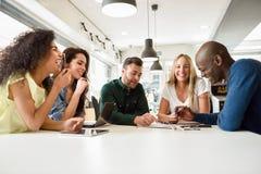Multiethnische Gruppe junge Leute, die zusammen auf weißem De studieren stockfoto