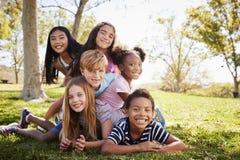 Multiethnische Gruppe Kinder, die auf einander in einem Park liegen stockfotografie