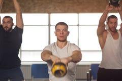 Multiethnische Gruppe männliche Athleten, die mit Kettlebells in der Turnhalle ausbilden stockfoto