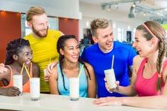Multiethnische Gruppe nette Freunde, die Proteindrinks trinken stockfotografie