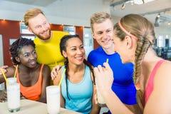 Multiethnische Gruppe nette Freunde, die Proteindrinks trinken stockfoto