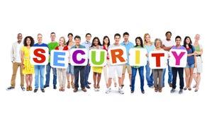 Multiethnische Gruppe von Personen, die Alphabet hält, um Sicherheit zu bilden Lizenzfreie Stockfotos