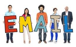 Multiethnische Gruppe von Personen, die Buchstabe-E-Mail hält Stockfotos