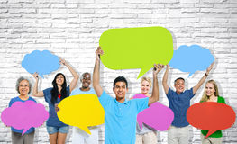 Multiethnische Gruppe von Personen, die bunte Sprache-Blasen hält Stockfotos