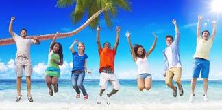 Multiethnische Gruppe von Personen, die durch den Strand springt Stockfotos