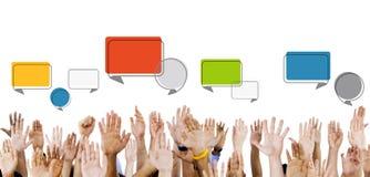 Multiethnische Hände angehoben mit Sprache-Blasen Lizenzfreie Stockfotografie