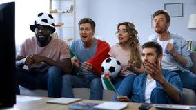 Multiethnische italienische Fans, die auf Sofa und aufpassendem Spiel, Stützteam sitzen stockfotos