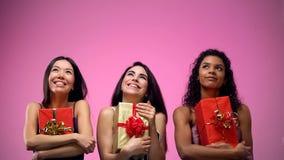 Multiethnische junge Damen, die Geschenke halten und oben, Feiertagsfeier schauen stockfotos