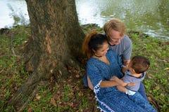 Multiethnische junge Familie, die zusammen am Park verpfändet stockbild