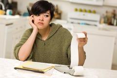 Multiethnische junge Frau, die über Finanzverhältnissen kämpft Lizenzfreies Stockfoto