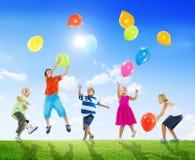 Multiethnische Kinder, die draußen Ballone spielen Stockfoto