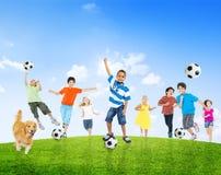 Multiethnische Kinder, die draußen Fußball spielen Stockfotografie