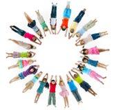 Multiethnische Kinder, die sich hinlegen und Kreis bilden lizenzfreie stockfotos