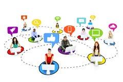 Multiethnische Leute, die an Social Media-Symbole anschließen Lizenzfreie Stockfotografie