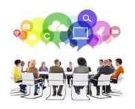 Multiethnische Leute in einer Sitzung mit Social Media-Symbolen Stockfoto