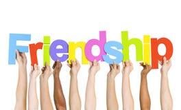 Multiethnische Leute, welche die Wort-Freundschaft halten Lizenzfreie Stockbilder