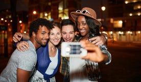 Multiethnische millenial Gruppe Freunde, die ein selfie Foto mit Handy auf Dachspitze terrasse unter Verwendung des Blitzes nacht Lizenzfreie Stockbilder