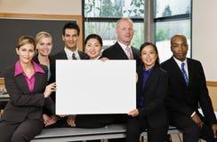 Multiethnische Mitarbeiter, die mit unbelegtem Zeichen aufwerfen Lizenzfreie Stockbilder