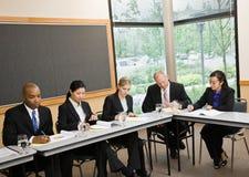 Multiethnische Mitarbeiter, die um Tabelle sitzen Lizenzfreie Stockfotos