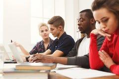 Multiethnische Mitschüler, die sich zusammen für Prüfungen vorbereiten stockfotografie