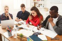 Multiethnische Mitschüler, die sich zusammen für Prüfungen vorbereiten stockbild