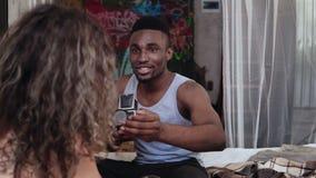 Multiethnische Paare auf dem Bett am Morgen Der junge gutaussehende Mann, der Fotos auf dem alten photocamera macht, Frau wirft a Lizenzfreies Stockbild