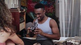 Multiethnische Paare auf dem Bett am Morgen Der junge gutaussehende Mann, der Fotos auf dem alten photocamera macht, Frau wirft a Lizenzfreie Stockfotografie