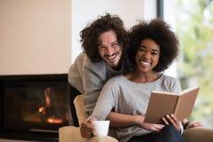 Multiethnische Paare, die vor Kamin umarmen lizenzfreies stockfoto