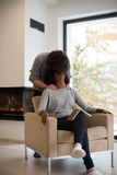 Multiethnische Paare, die vor Kamin umarmen lizenzfreies stockbild