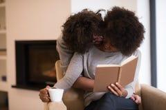 Multiethnische Paare, die vor Kamin umarmen lizenzfreie stockfotos