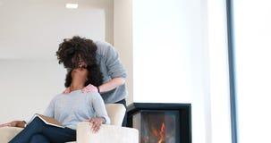 Multiethnische Paare, die vor Kamin umarmen lizenzfreie stockbilder