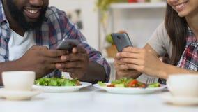 Multiethnische Paare unter Verwendung der Smartphones während des Abendessens, Mangel an wirklicher Kommunikation stock footage