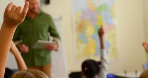 Multiethnische Schulkinder, die H?nde beim am Schreibtisch in einem Klassenzimmer 4k in der Schule sitzen anheben stock footage