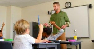 Multiethnische Schulkinder, die H?nde beim am Schreibtisch in einem Klassenzimmer 4k in der Schule sitzen anheben stock video footage