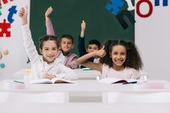 Multiethnische Schulkinder, die oben Daumen beim Sitzen an den Schreibtischen im Klassenzimmer zeigen stockbild