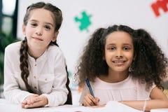 Multiethnische Schulmädchen, die an der Kamera beim im Klassenzimmer zusammen studieren lächeln Stockfotos
