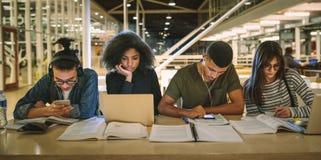 Multiethnische Studenten, die an der Collegebibliothek sitzen stockbilder
