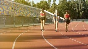 Multiethnische Studentinnen, die zum Umkleideraum nach Training am Stadion gehen lizenzfreies stockfoto