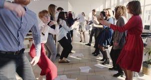 Multiethnische Unternehmensgeschäftsleute des glücklichen Spaßes, die zusammen in das moderne helle Büro feiert Feiertage und Erf stock video