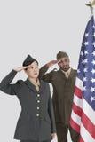 Multiethnische US-Militäroffiziere, die amerikanische Flagge über grauem Hintergrund begrüßen Stockfotos