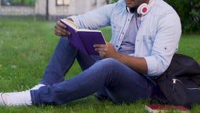 Multiethnischer Mann, der auf Graslesebuch, entspannende Tätigkeit, Bücherwurm sitzt stock video