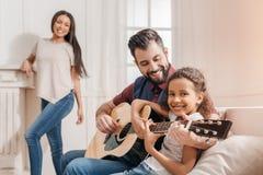 Multiethnischer Vater und Tochter, die zu Hause Gitarre auf Sofa spielt Lizenzfreie Stockfotos