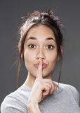 Multiethnisches Mädchen des Spaßes, das bittet, für Diskretion auf stille Art zu halten lizenzfreie stockfotografie