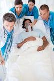 Multiethnisches Notteam, das einen Patienten trägt Lizenzfreie Stockfotos