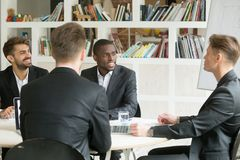 Multiethnisches Team von den männlichen Mitarbeitern, die Unternehmenspläne DU besprechen Stockfotos