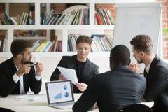 Multiethnisches Team von den männlichen Mitarbeitern, die Unternehmenspläne DU besprechen Stockbilder