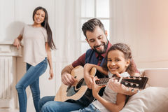 Multietnisk fader och dotter som hemma spelar gitarren på soffan Royaltyfria Foton