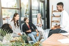 multietnisk grupp av affärscoworkers som har konversation under kaffeavbrott arkivbilder