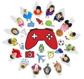 Multietnisk grupp av barn som spelar videospel Arkivbild